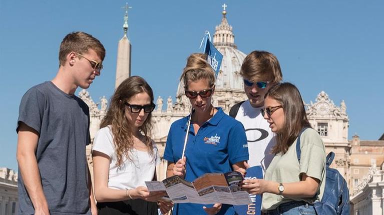 Guida con alcuni visitatori all'esterno dei Musei Vaticani a Roma